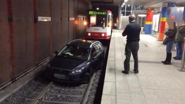 Ivre, il suit un tramway avec sa voiture et s'arrête sur les voies dans une station