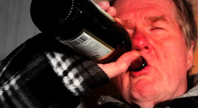 Ivre, il mange une bouteille de bière en verre