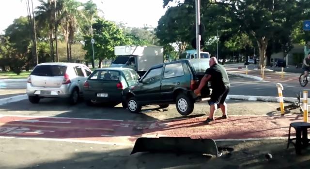 Il déplace une voiture garée sur une piste cyclable en la soulevant avec ses mains